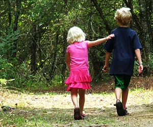 Brother and sister walk in woods